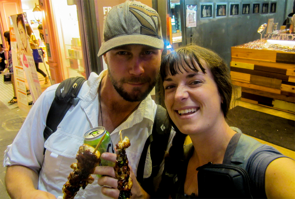 Mark and Kylee holding some chicken skewers on a street in Korea.