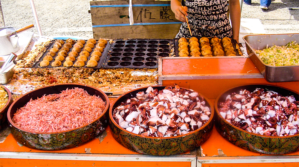 A layout of ingredients including octopus, onions, and batter.
