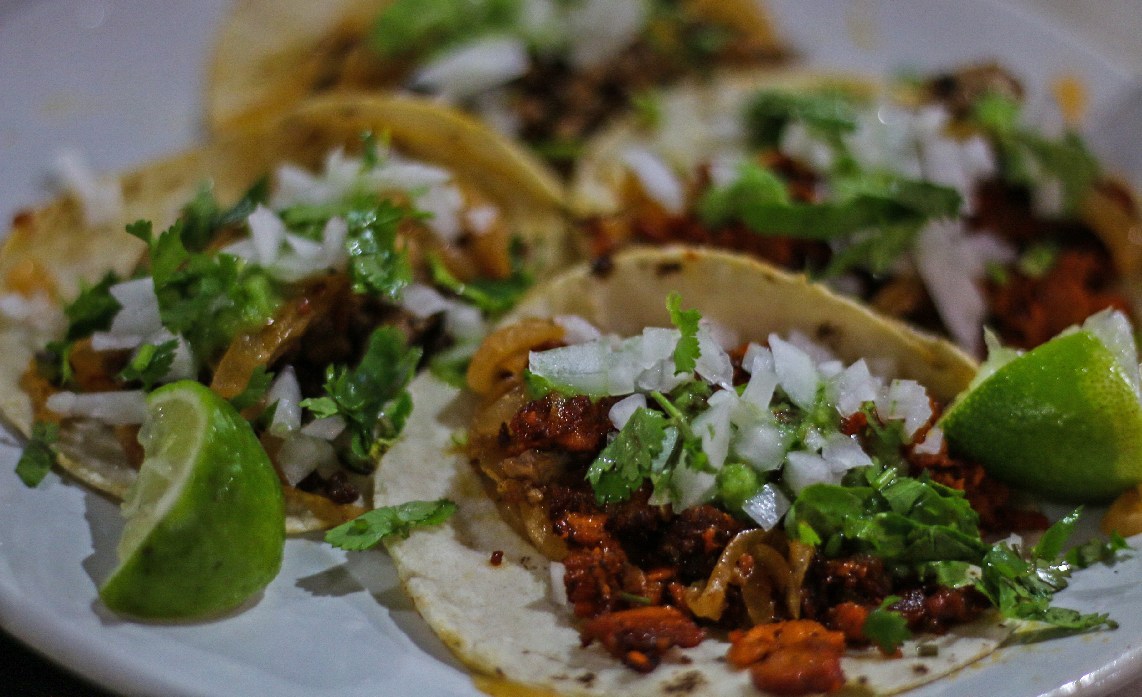 A plate of pork and beef tacos topped with onions and cilantro