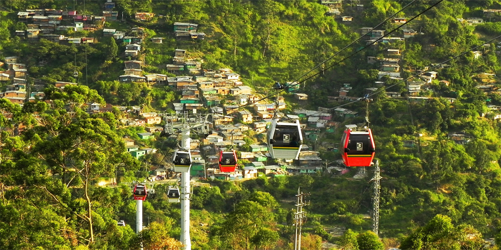 A view of a gondola from above with some buildings of Medellin below in the background