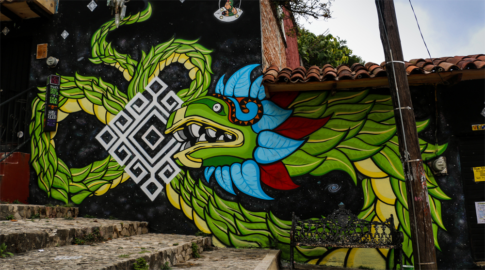 A green dragon painted on a wall along some stone steps.