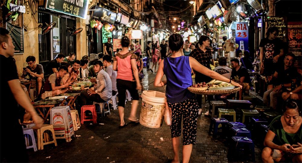 A dark street in Vietnam with food vendors and people eating street food.