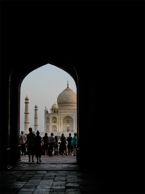 A dark hallway with an arch at the end, through the arch is a group of people looking at the Taj Mahal