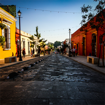 A quiet street lined with colourful buildings at sunset