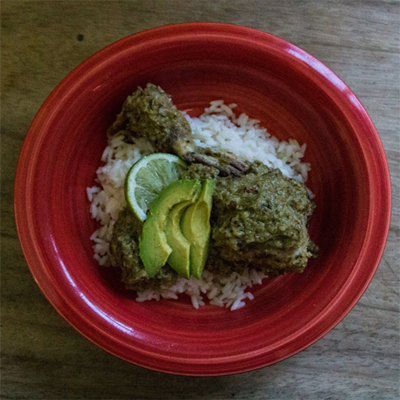 Red bowl filled with rice topped with chicken and avocado.