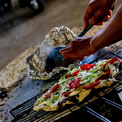 A tortilla with several toppings being grilled over a charcoal grill.