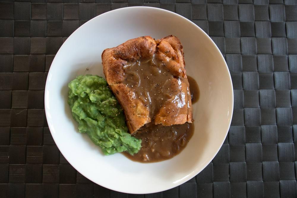 Toad in a hole, sausage in Yorkshire pudding with gravy and mushy peas.