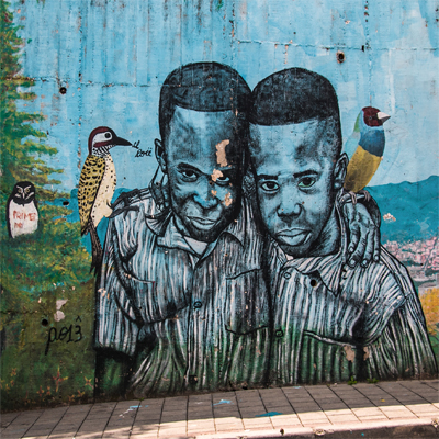 A wall with a painting of two boys hugging. Birds are on their shoulders.
