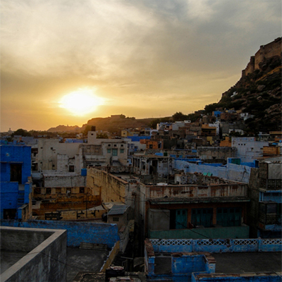Sunset over a city filled with many blue-painted buildings.