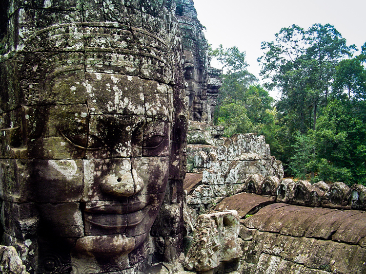 A face carved out of stone on a large temple in the jungle