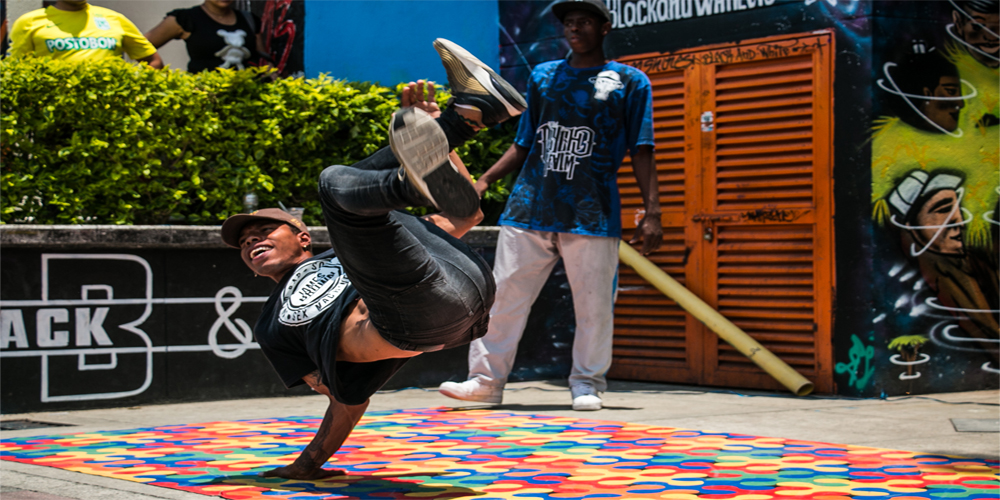A break-dancer preforms on the side of the road