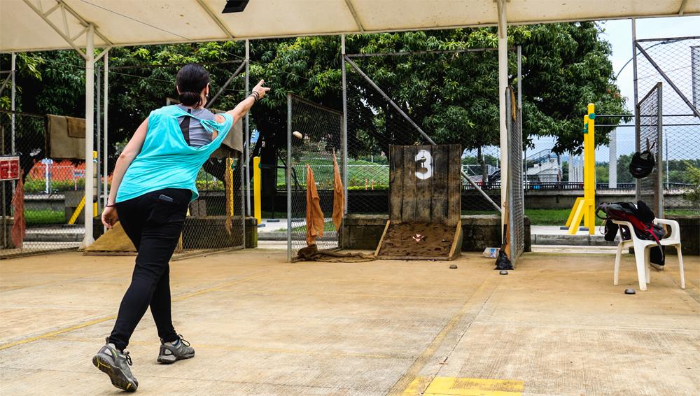 A woman throwing a metal puck towards a target