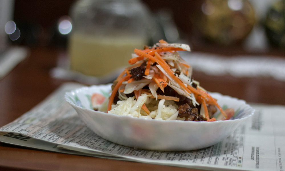 A bowl of mashed root vegetable with crispy pieces of pork and a carrot slaw